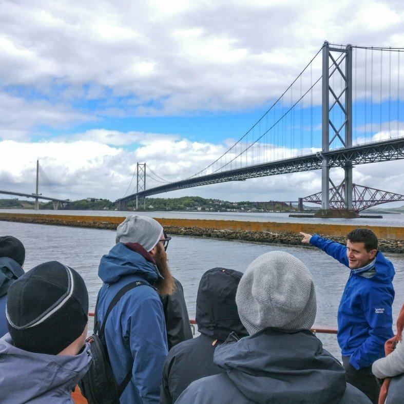 Engineer explaining the Forth Bridges to a group tour near Edinburgh